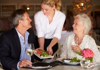 Waitress Serving Food To Senior Couple In Restaurant during a bridge tournament