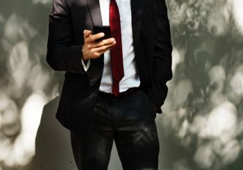 Man Standing Holding Smartphone - Great Bridge Links